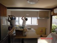 古いキッチンと吊戸棚を解体し、キッチンパネルを貼り付けていきます。