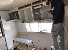 壁にはキッチンパネルを貼り、新しい吊戸棚やレンジフードを取り付けていきます。