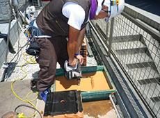 先程取り外した瓦に穴を開けます。必ず地上作業で行い、瓦を削った粉が飛び散らないよう水に濡らしながら穴を開けます。