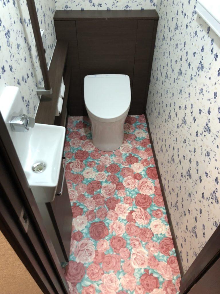 タンクレストイレになり、床に置いていた小物類も背面のキャビネットに収納し、スッキリとした奥行きのある空間になりました。 奥さまのお好みの花柄でゴージャスな室内になりましたね。